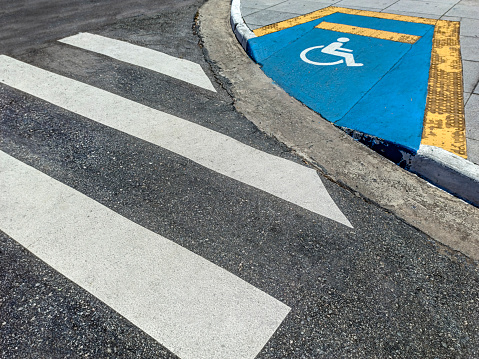 Accessibility ramp for wheelchair users on street sidewalk with indication of use, with a crosswalk