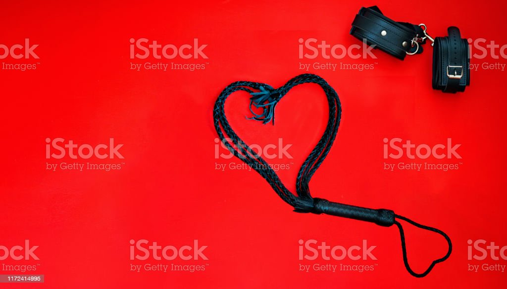 Accessories for bdsm on a red leather background. Lash in the shape of a heart and leather handcuffs. Valentine's Day. Erotic shop. Copy space. free space mockup Accessories for bdsm on a red leather background. Lash in the shape of a heart and leather handcuffs. Valentine's Day. Erotic shop. Copy space. free space mockup. Black Color Stock Photo