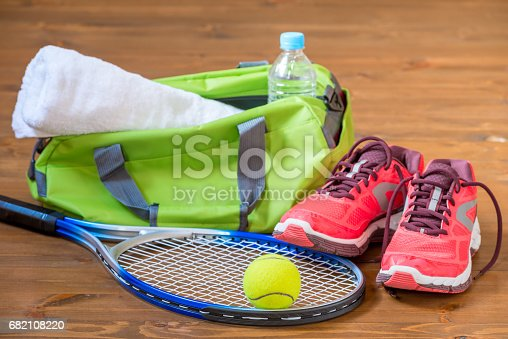 istock Accessories for playing tennis lie on the wooden dark floor 682108220