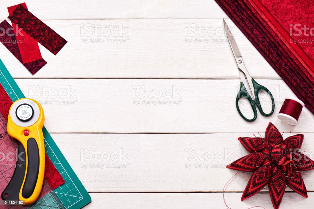 Accessories for quilting on a white wooden surface, top view stock photo