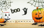 istock Accessories of decorations Happy Halloween day background concept.Cup of drink with pumpkin object to party season with spider on modern rustic brown & white backdrop at home office desk studio. 1178690795
