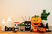 istock Accessories of decorations Happy Halloween day background concept.Cup of drink with pumpkin object to party season with spider on modern rustic brown & white stone backdrop at home office desk studio. 1180966942