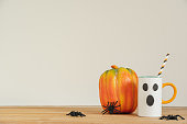 istock Accessories of decorations Happy Halloween day background concept.Cup of drink with pumpkin object to party season with spider on modern rustic brown & white backdrop at home office desk studio. 1199808521