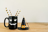 istock Accessories of decorations Happy Halloween day background concept.Jack O Lanterns cup of drink with Witch's broom of object to party season on modern rustic brown & white stone backdrop.copy space. 1179502266