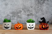 istock Accessories of decorations Happy Halloween day background concept.Jack O Lanterns cactus with spooky pumpkins object to party season with spider on modern rustic brown & white stone backdrop. 1179502279