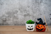 istock Accessories of decorations Happy Halloween day background concept.Jack O Lanterns cactus with spooky pumpkins object to party season with witch's broom on modern rustic brown & white stone backdrop. 1179502280