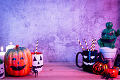 istock Accessories of decorations Happy Halloween day background concept.Jack O lantern of Cup of drink with pumpkin objects to party season with spider on brown & stone backdrop at home office desk studio. 1179502287