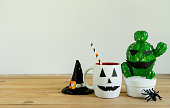 istock Accessories of decorations Happy Halloween day background concept.Jack O Lanterns cactus with ghost object to party season with hat witch & cup drink on modern rustic brown & white stone backdrop. 1180966915