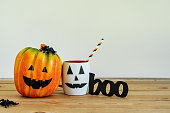 istock Accessories of decorations Happy Halloween day background concept.Jack O Lanterns cup of drink with boo text and pumpkins of object to party season on modern rustic brown & white stone backdrop. 1180966919