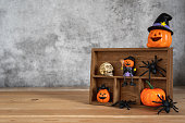 istock Accessories of decorations Happy Halloween day background concept.Jack O lantern pumpkin objects on shelf wood to party season with spider and skeleton on brown wooden & stone backdrop.copy space. 1180966921