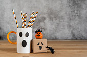 istock Accessories of decorations Happy Halloween day background concept.Jack O Lanterns cup of drink with gift box pumkin of object to party season on modern rustic brown & white stone backdrop.copy space. 1180966944