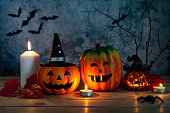 istock Accessories of decorations Happy Halloween day background concept.Jack O lantern pumpkin objects and light candle to party season with spider on brown & stone backdrop at home office desk studio. 1180966953