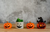 istock Accessories of decorations Happy Halloween day background concept.Jack O Lanterns cactus with spooky pumpkins object to party season with spider on modern rustic brown & white stone backdrop. 1182392699