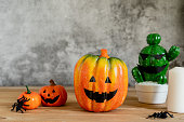 istock Accessories of decorations Happy Halloween day background concept.Jack O Lanterns cactus with spooky pumpkins object to party season with spider on modern rustic brown & white stone backdrop. 1182392720