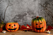 istock Accessories of decorations Happy Halloween day background concept.Jack O lantern pumpkin objects and light candle to party season with spider on brown & stone backdrop at home office desk studio. 1182392750