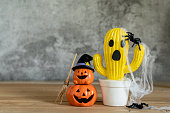 istock Accessories of decorations Happy Halloween day background concept.Jack O Lanterns cactus with spooky pumpkins object to party season with spider on modern rustic brown & white stone backdrop. 1182392752