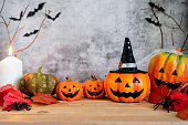 istock Accessories of decorations Happy Halloween day background concept.Jack O lantern pumpkin objects and light candle to party season with spider on brown & stone backdrop at home office desk studio. 1182392785