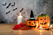 istock Accessories of decorations Happy Halloween day background concept.Jack O lantern pumpkin objects and light candle to party season with spider on brown & stone backdrop at home office desk studio. 1182393382