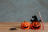 istock Accessories of decorations Happy Halloween day background concept.Couple jack O Lanterns with spooky pumpkins with witch broom object to party season  on modern  brown & white stone backdrop. 1180966954