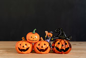 istock Accessories of decorations Happy Halloween day background concept.Variety of Jack O Lanterns pumpkins object to party season with spider on modern rustic brown & black stone backdrop.copy space. 1179502315