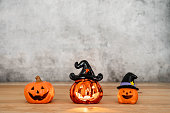istock Accessories of decorations Happy Halloween day background concept.Variety of Jack O Lanterns pumpkins object candle to party season on modern rustic brown wooden & black stone backdrop.copy space. 1180966918