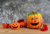 istock Accessories of decorations Happy Halloween day background concept.Variety of Jack O Lanterns pumpkins object to party season with autumn leaves on modern rustic brown & white stone backdrop.copy space 1182393275