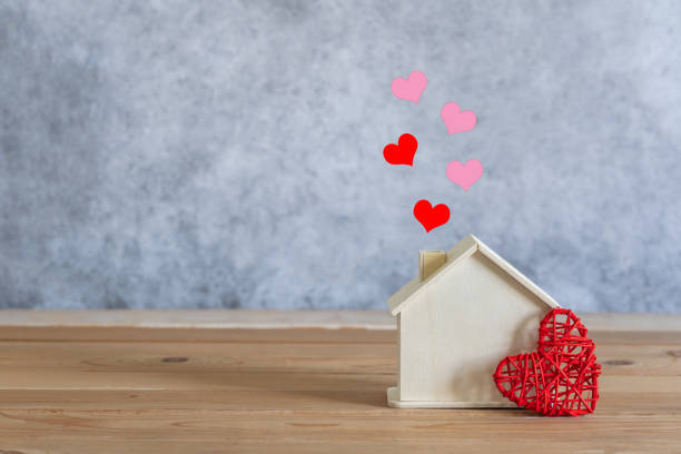 Accessories of decorations valentine's day holiday background concept.Essential items colorful pastel love shape with wooden house on modern rustic brown wooden.Copy space for creative design text. stock photo