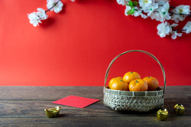 accessories on lunar new year & chinese new year vacation concept background.orange in wood basket with  red pocket money and flower on modern rustic brown & red backdrop at home office desk studio. - chinese new year stock pictures, royalty-free photos & images