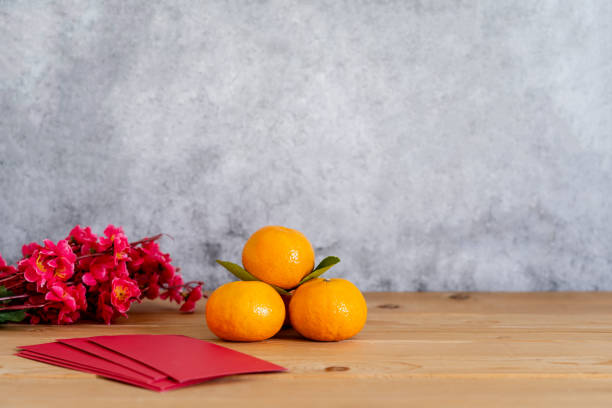 Accessories on Lunar New Year & Chinese New Year vacation concept holiday background.Orange in wood basket with plum blossom and red packet on modern rustic brown & grey stone backdrop.space for text. stock photo
