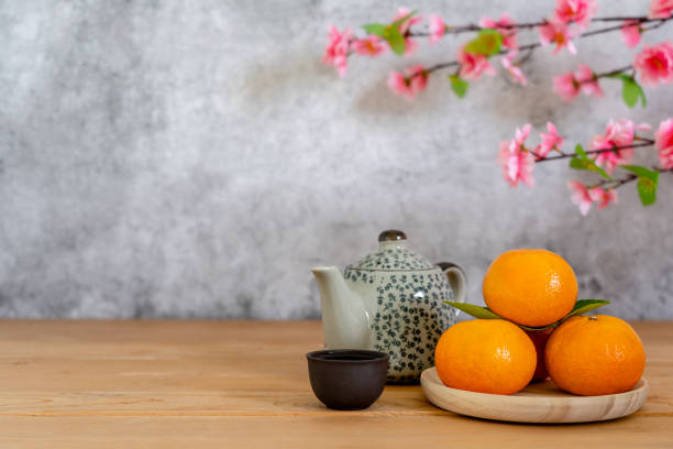 Accessories on Lunar New Year & Chinese New Year vacation concept holiday background.Orange in wood basket with  tea pot and pink plum blossom on modern rustic brown wooden & grey stone backdrop. stock photo