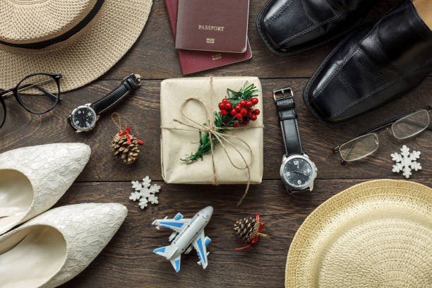 Accessory men & women to travel Christmas and Happy new year concept background.Top view shot of sign winter season.Essential items for couple traveler & backpacker adult or teenage to holidays trip. stock photo