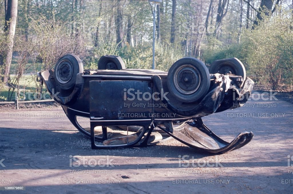 Accident car in the Berlin Tiergarten Tiergarten, Berlin West, Germany, 1977. Accident car lying on the roof. 1970-1979 Stock Photo