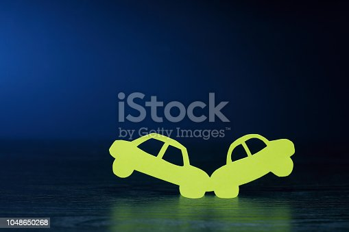 Crush of two cars made from yellow paper on dark background