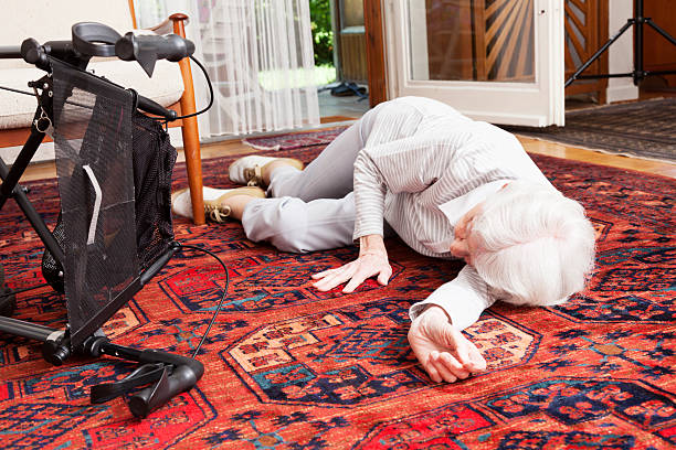 accident senior woman after fall lying on ground stock photo
