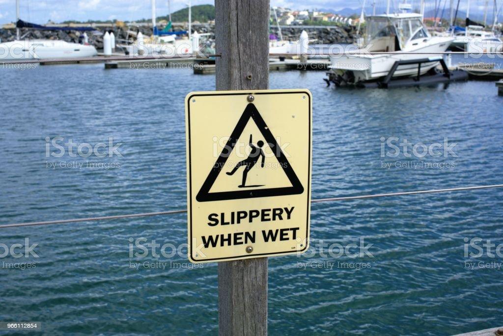 Varning tecken av olyckor nära vatten hala när det är vått - Royaltyfri Ansvar Bildbanksbilder