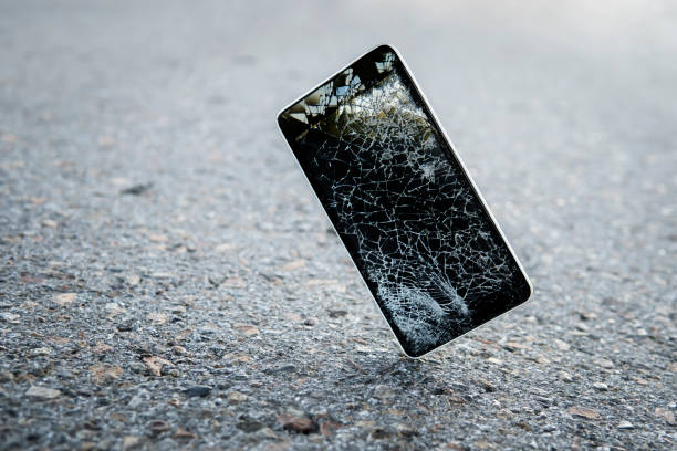 Accident with gadget concept. Device need repairing. Copy space. Mobile phone falling and crashes on asphalt, broken smartphone flying down to ground. Smashed, destroyed, damaged cellphone. stock photo