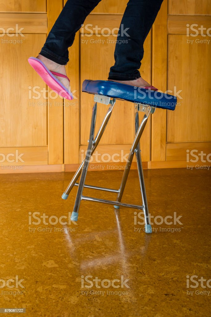 Accident - woman falling from a stool stock photo