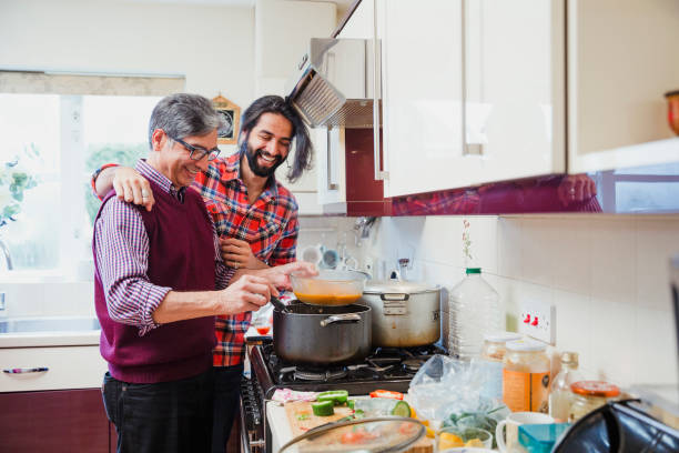 Accompanying Dad While he Cooks Mid adult man is looking over his father's shoulder as he prepares a curry at home. balti dish stock pictures, royalty-free photos & images