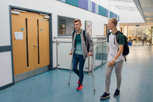 accompanying friend at school - broken leg stock photos and pictures