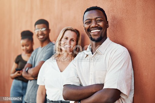 Cropped portrait of a handsome young businessman standing with his colleagues against a wall outside