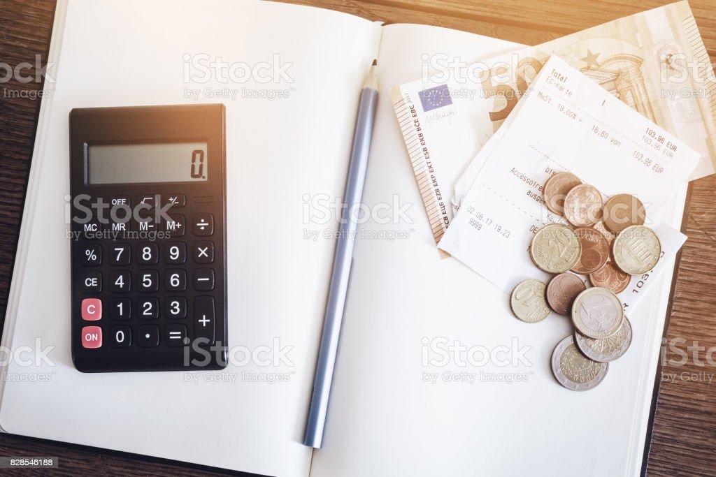 Konto-Buch-Konzept mit Münzen und Cash-Wechsel, Notebook und Rechner auf tirolerische Holztisch – Foto