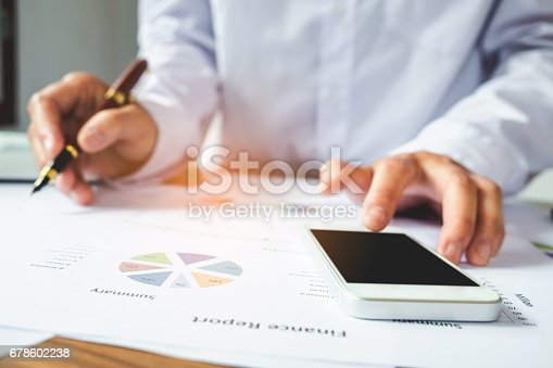 istock Account manager using mobile phone. Typing contemporary smartphone screen and pointing on summary report chart 678602238