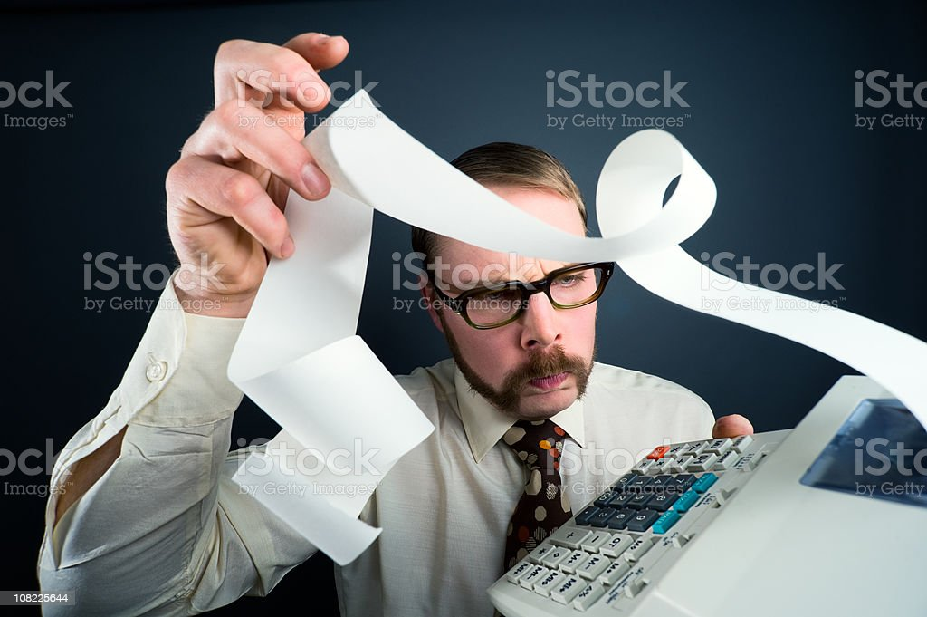 Accountant Adding Numbers on Calculator stock photo
