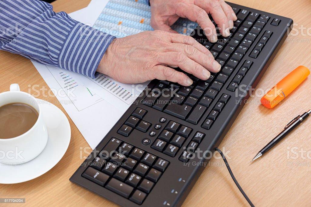 Accountant at his desk using a computer keyboard stock photo