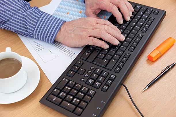 Comptable dans son bureau grâce à un clavier d'ordinateur - Photo