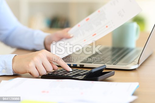490632340istockphoto Accountant calculating with a calculator on a desk 944129986