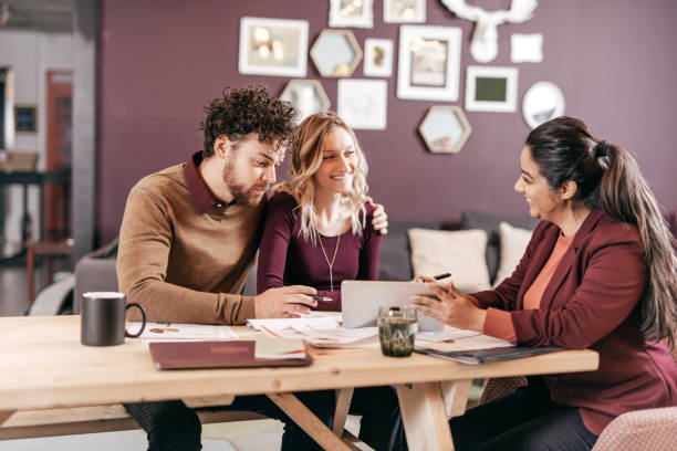 Accountant explaining taxes for couple Multiracial group indoor borrowing stock pictures, royalty-free photos & images