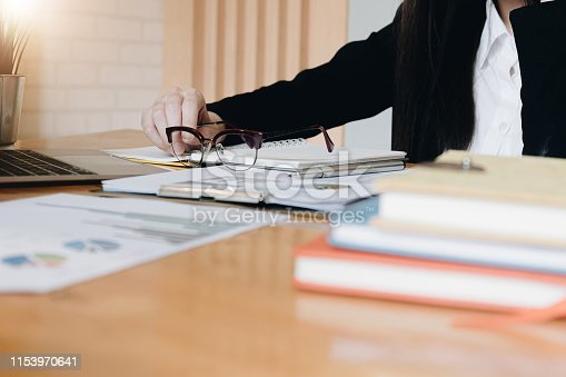 941729686istockphoto Accountant hand holding glasses during analyze statistics from financial documents 1153970641