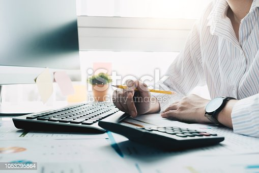 897852992istockphoto Accountant hand holding pencil working on calculator to calculate financial data report, accountancy document and laptop computer at office, business concept 1053295864