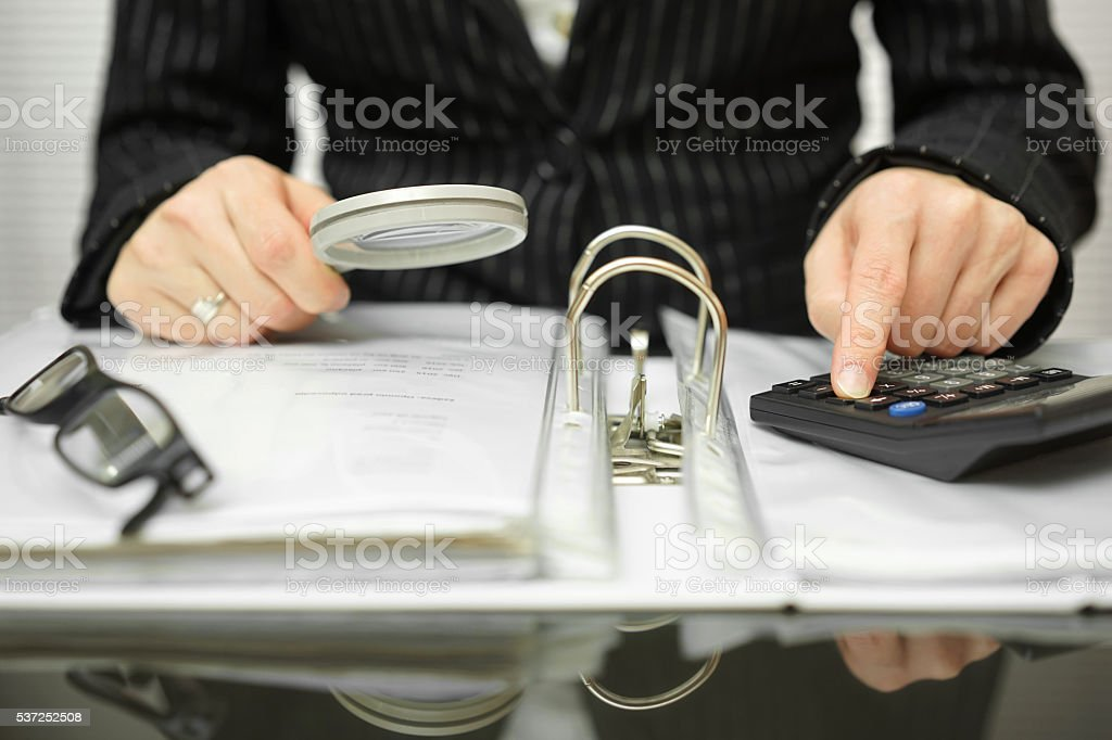accountant is examining  invoices and documents stock photo